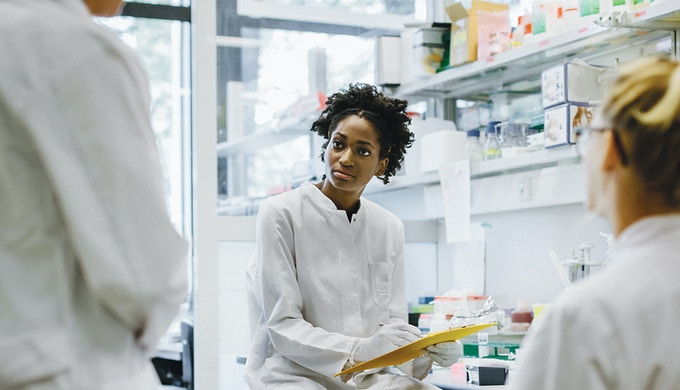 Three scientists having a team talk in a laboratory office discussing their work. A black scientistis holding a clipboard and writes down some data.