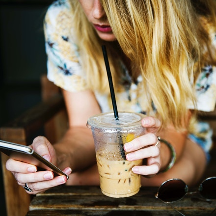Girl drinking coffee browsing phone